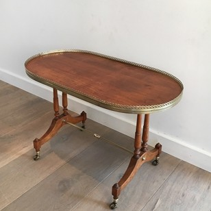 Neoclassical wood and brass oval coffee table.
