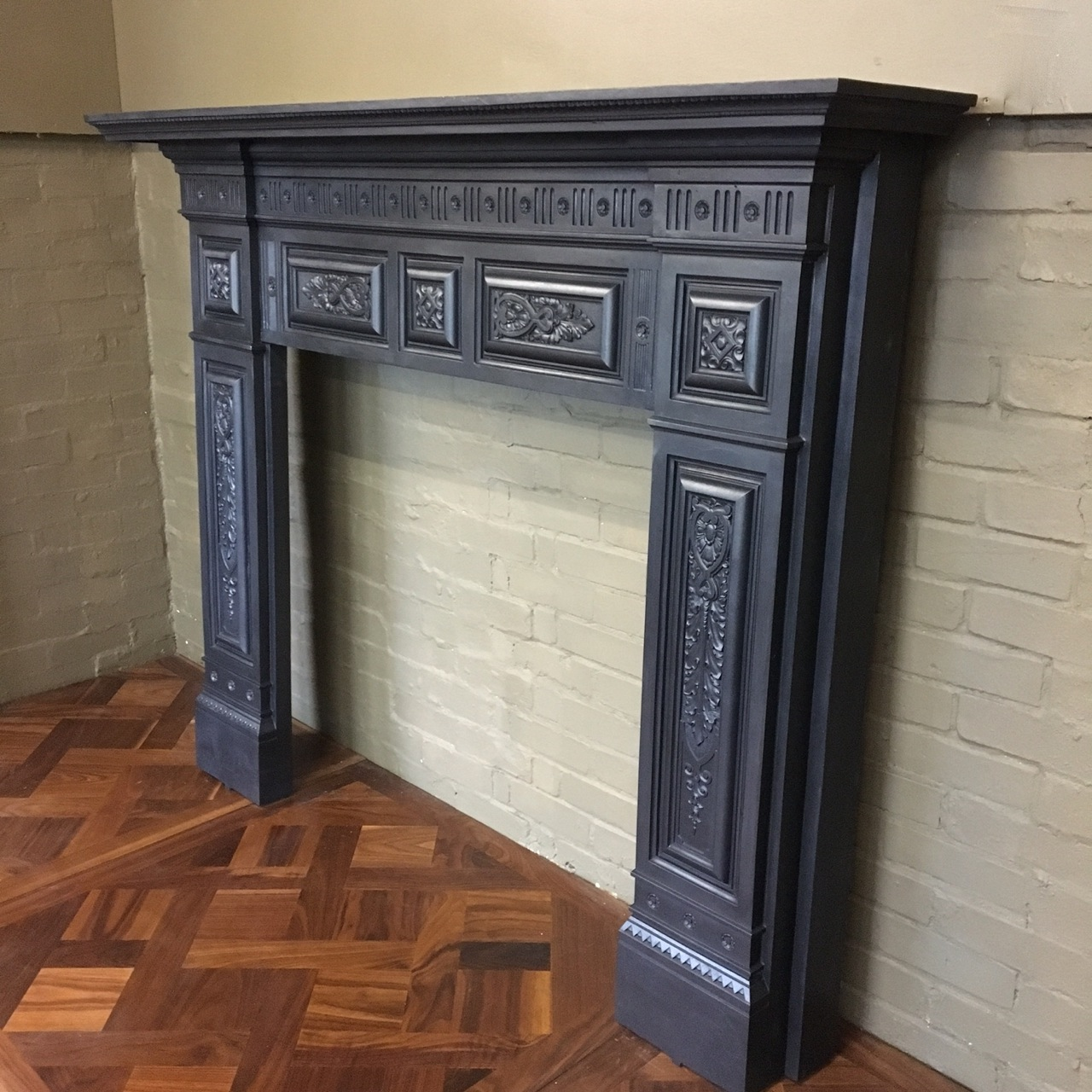 An antique late Victorian fireplace surround in cast iron. This original late Victorian or early Edwardian fire surround features panelled decoration across the lintel and jambs of the piece