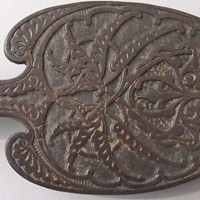A cast iron trivet by Christopher Dresser
